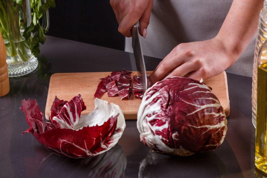 Roter Radicchio wird in der Küche geschnitten