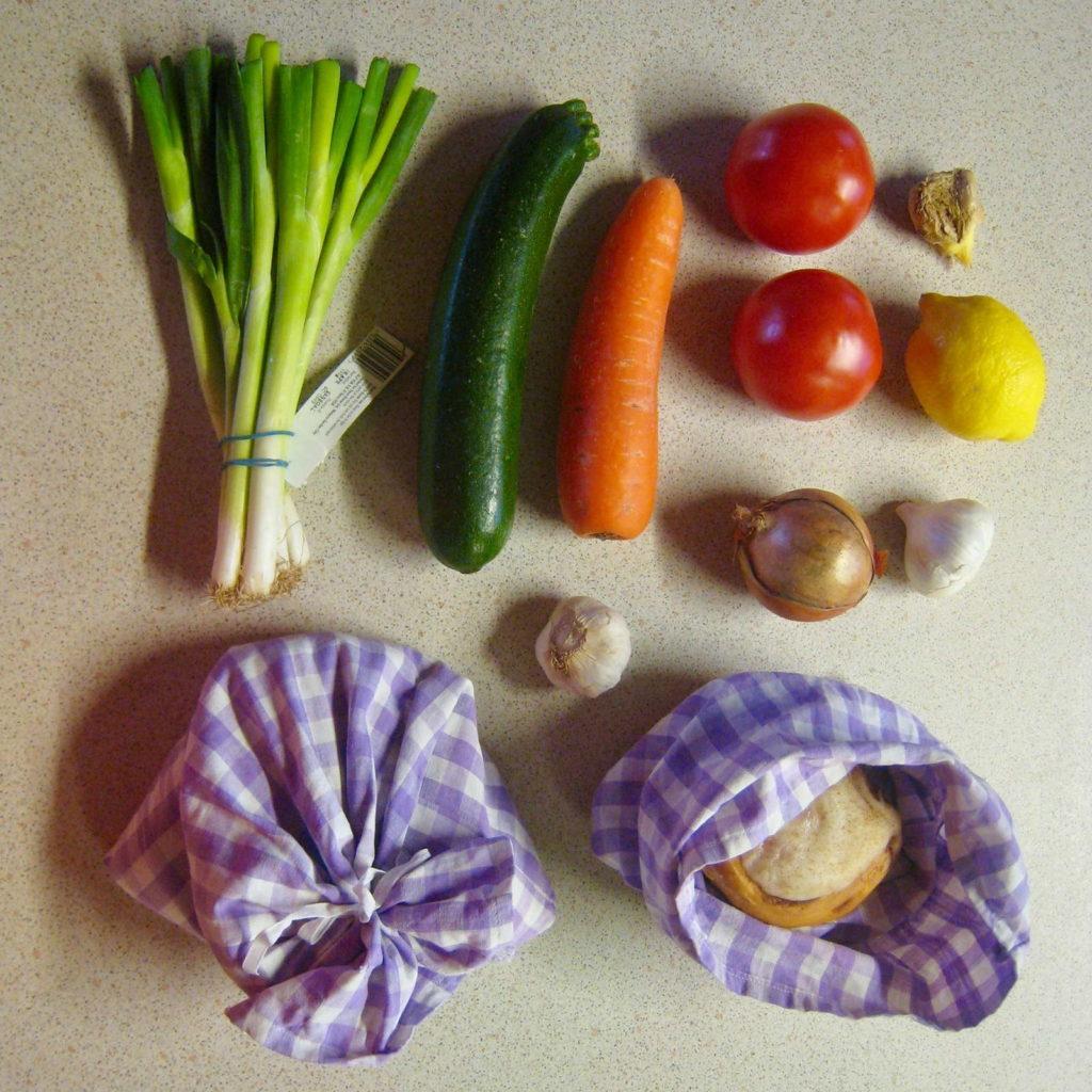 verpackungsfreier Einkauf Lauchzwiebeln Zucchini Karotte Tomaten Zwiebeln Zitrone Knoblauch Brot