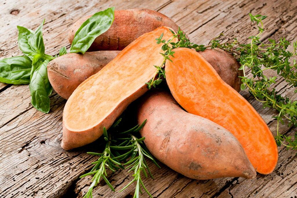 Süßkartoffeln auf Holztisch mit Kräutern