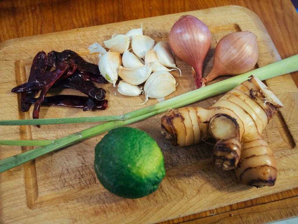 getrocknete Chillies, Knoblauch, Schallotten, Zitronengras, Limette und Galgant auf Holzbrett