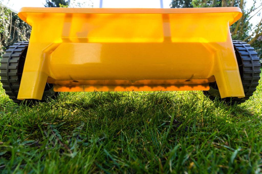 Rasen düngen gelber Düngerwagen Streuwagen
