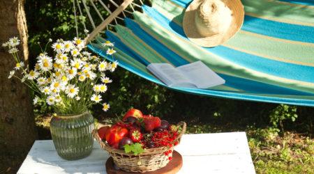 Blau gestreifte Hängematte mit weißem Hut und Früchten