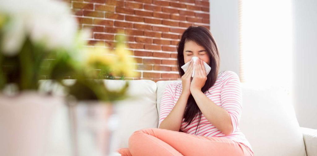 Frau niest im Wohnzimmer Zimmerpflanzen