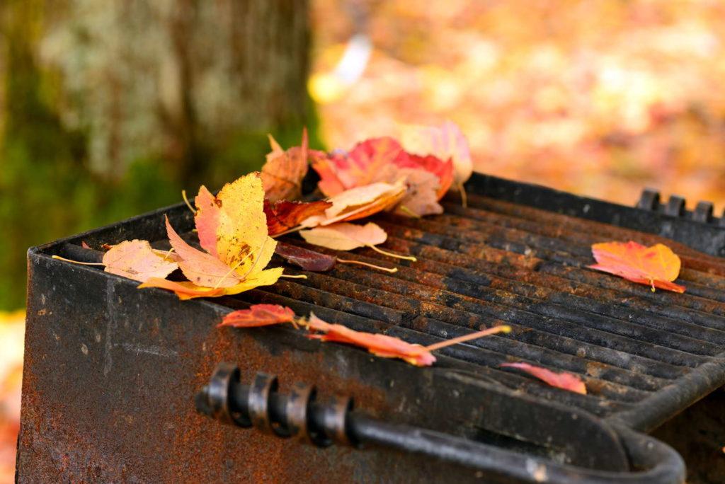Grill im Herbst draußen im Garten mit Blättern