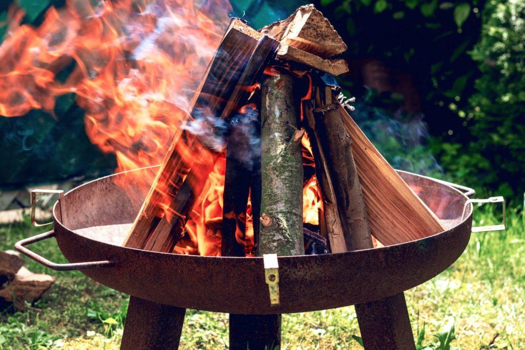 Feuerschale im Garten mit brennendem Holz