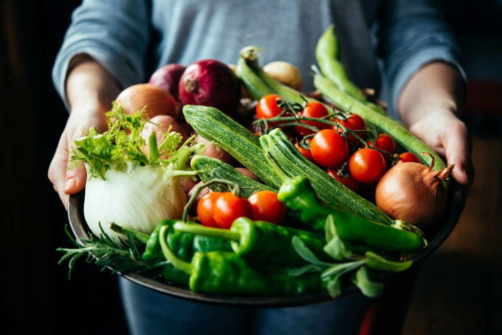 Verschiedenes Gemüse in Schale gehalten von Händen