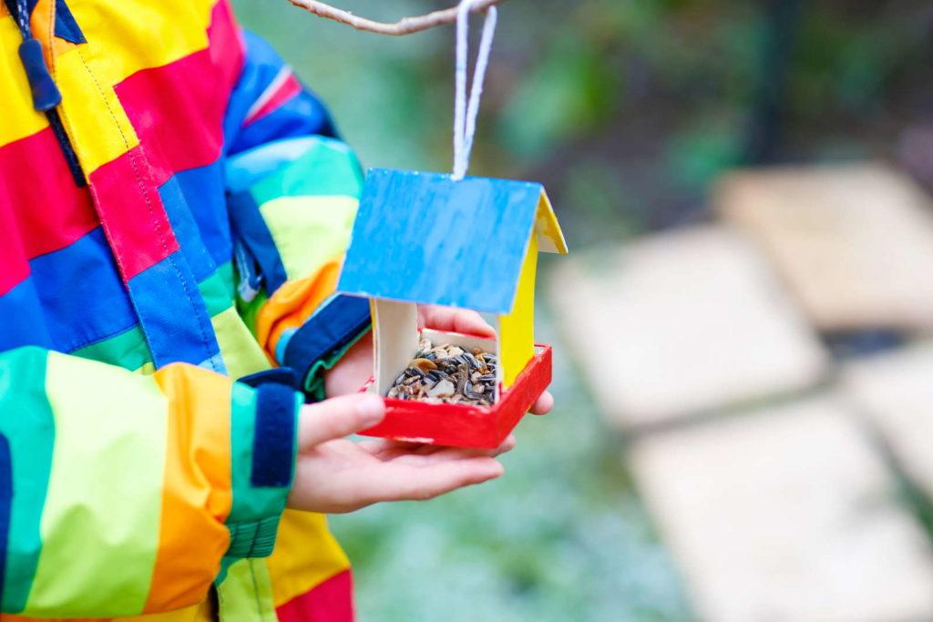 Kind mit Vogelhaus im Garten
