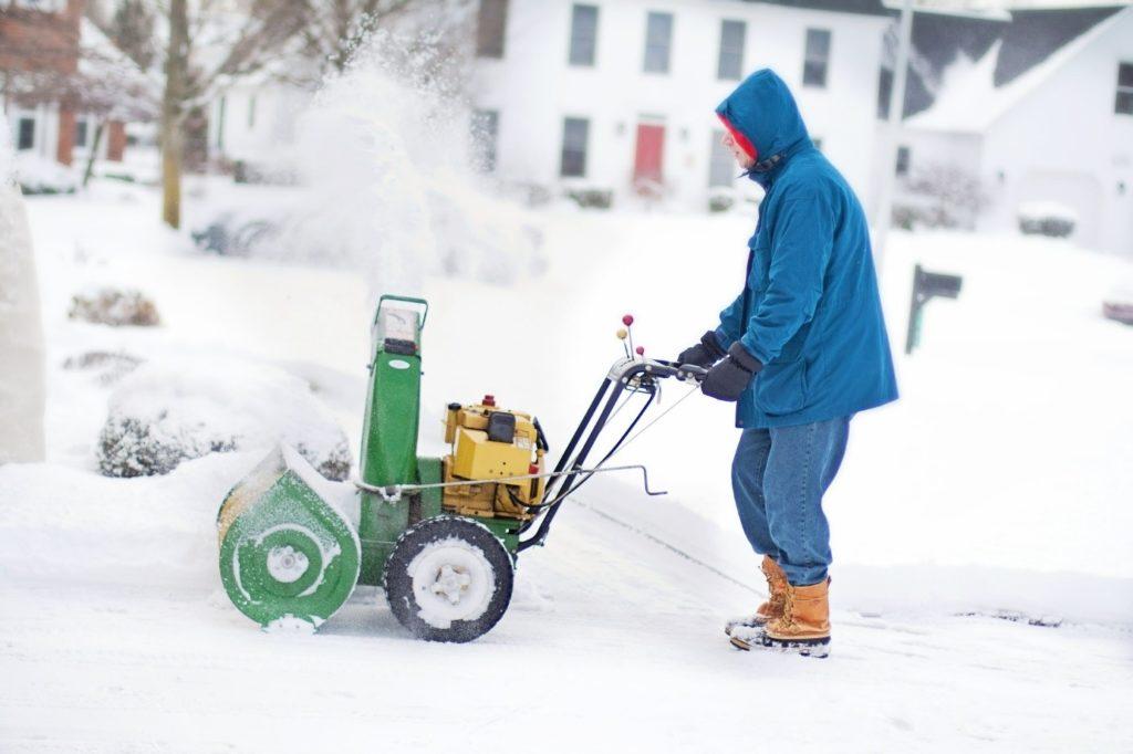 Mann mit Schneefräse im Schnee