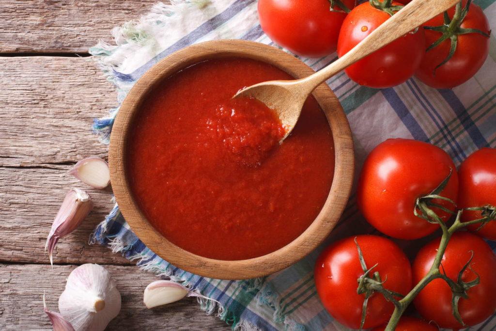 Tomatensoße in einer Holzschüssel mit frischen Tomaten