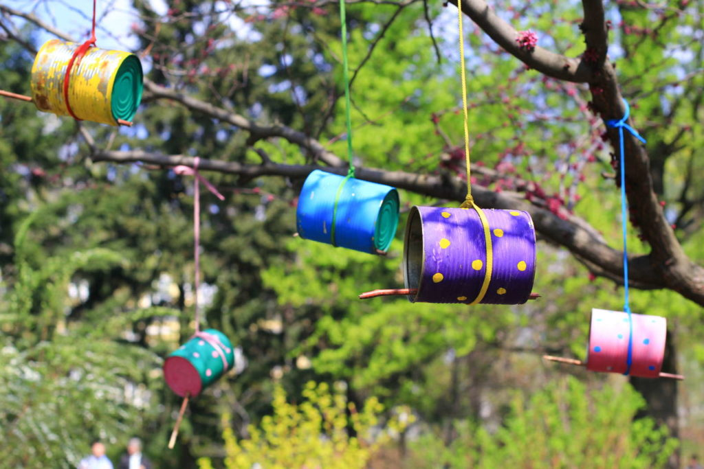 Vogelhäuser aus Dosen hängen an einem Baum im Garten