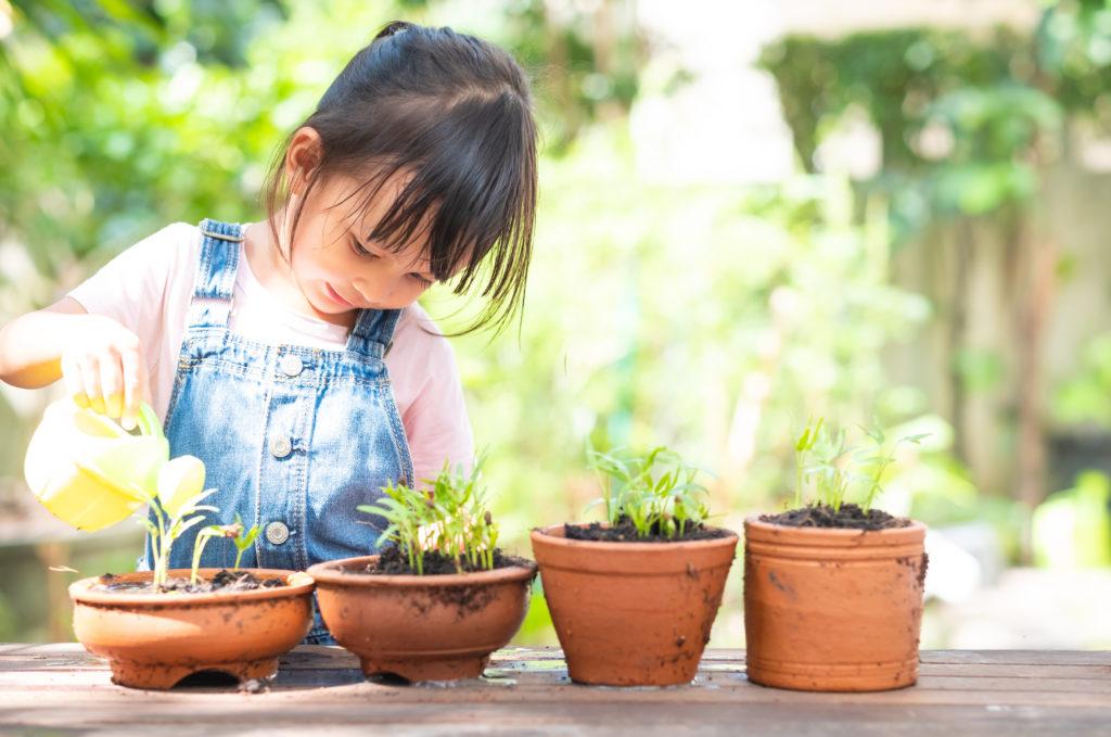 Kind mit Blumentöpfen Gießkanne