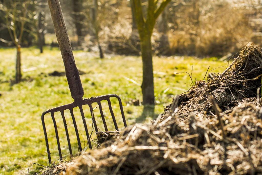 Kompost mit Mistgabel im Garten