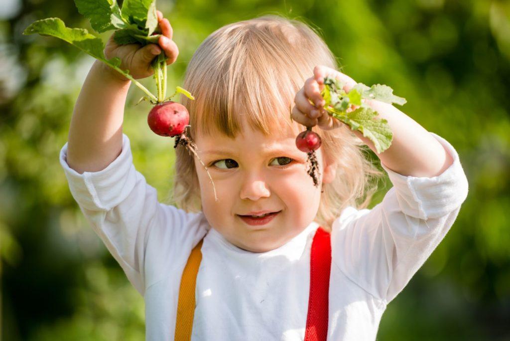 Mädchen mit Radiesschen Ernte