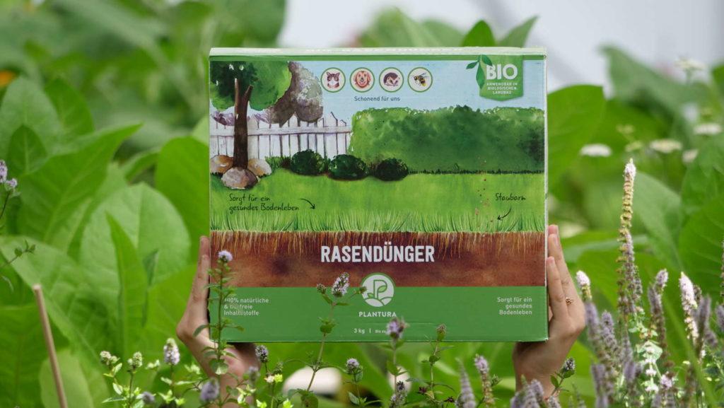 Rasendünger wird in Händen gehalten