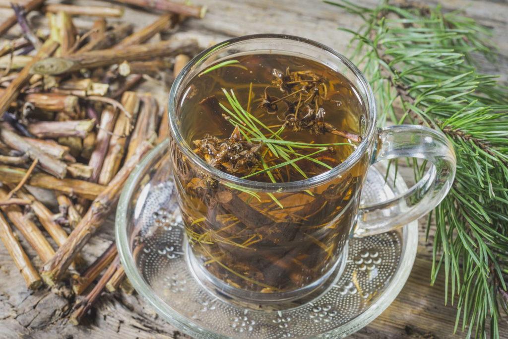 Tee aus Tannennadeln auf einem Holztisch