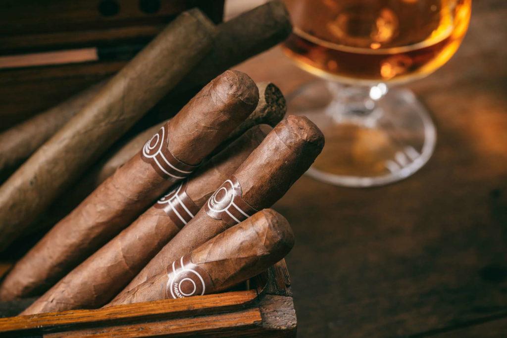 Zigarren in einer Holzkiste, im Hintergrund ein Glas mit Cognac