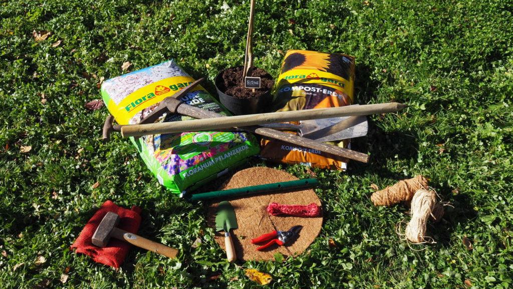 Werkzeug zum Einpflanzen eines Obstbaums auf grüner Wiese