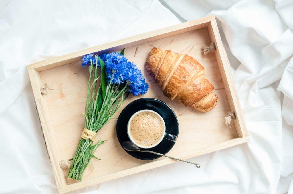 Kornblume auf einem Frühstücksbrett neben einem Croissant und Kaffee