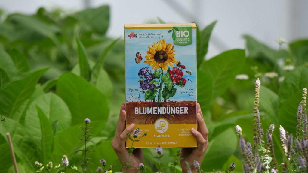 Plnatura Bio-Blumendünger wird hochgehalten