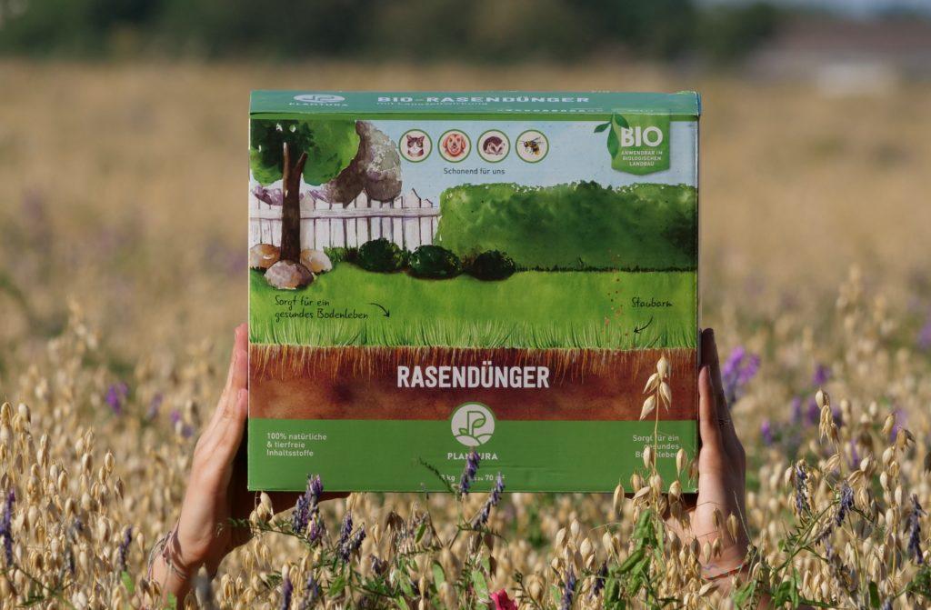 Unser Plantura Bio-Rasendünger wird in einem Feld hochgehalten