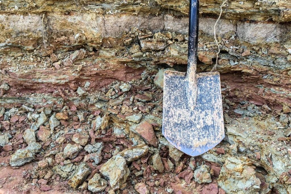 Schaufel vor Boden mit Eisenhaufen