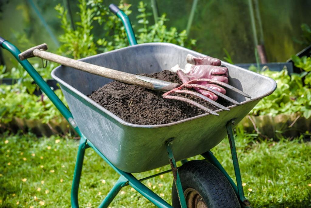 Kompost in Schubkarre mit Grabegabel