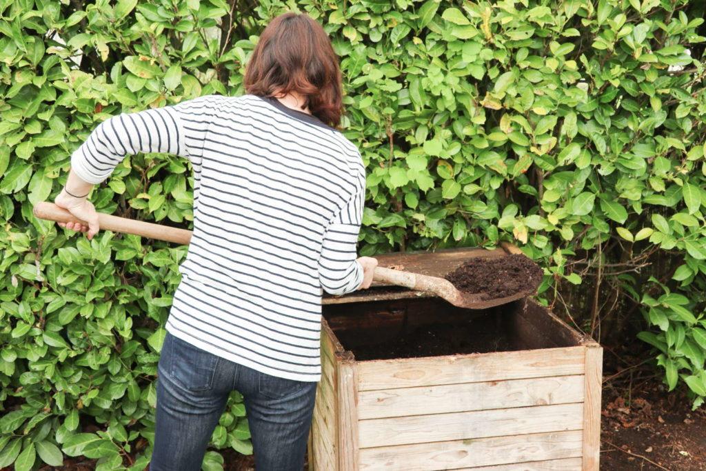 Kompost wird mit einem Spaten von einer Frau umgeschichtet
