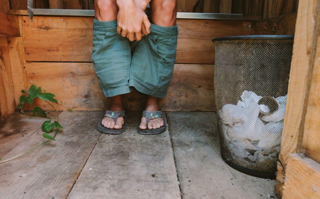 Mensch sitzt auf Komposttoilette