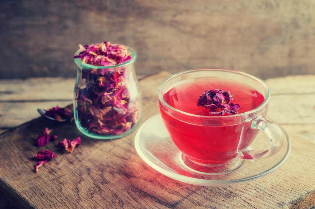 Tee aus Rosenblüten in Glastasse
