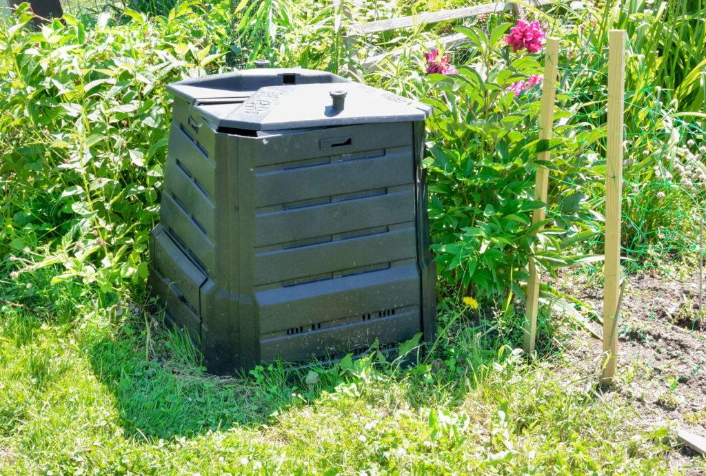 schwarzer Komposter in einem Garten