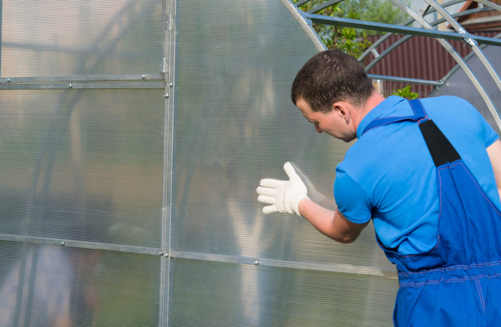workers in blue uniforms, checking the correct installation of the greenhouse and polycarbonate on it.