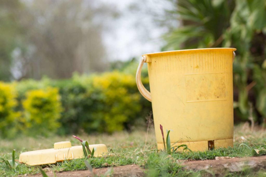 Gelber Mülleimer im Garten