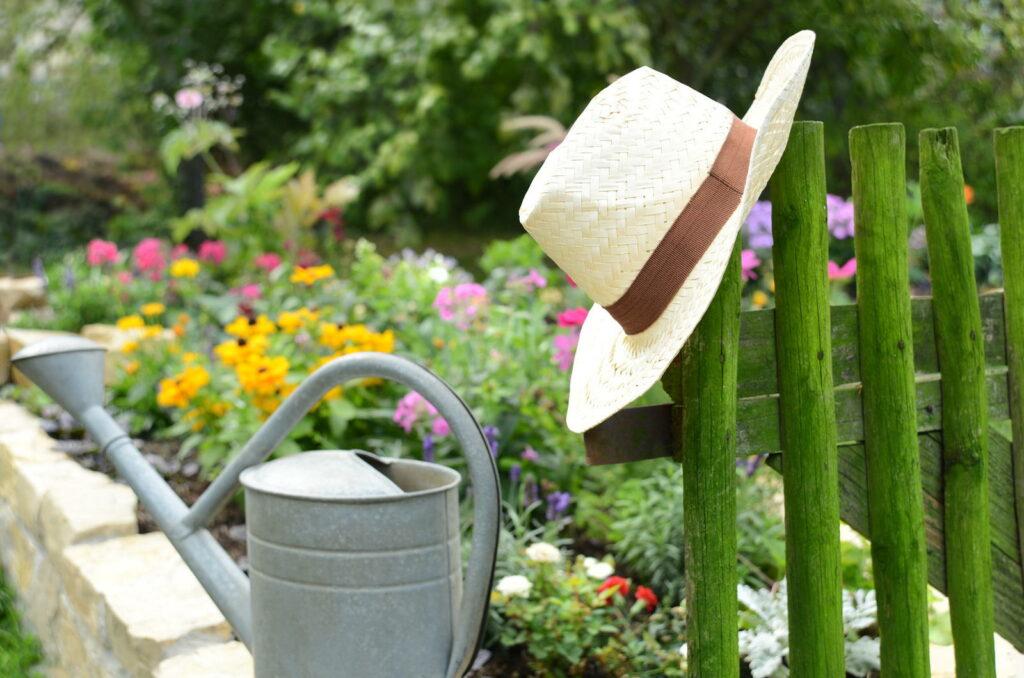 Sonennhut und Gießkanne mit einem grünen Gartenzaun
