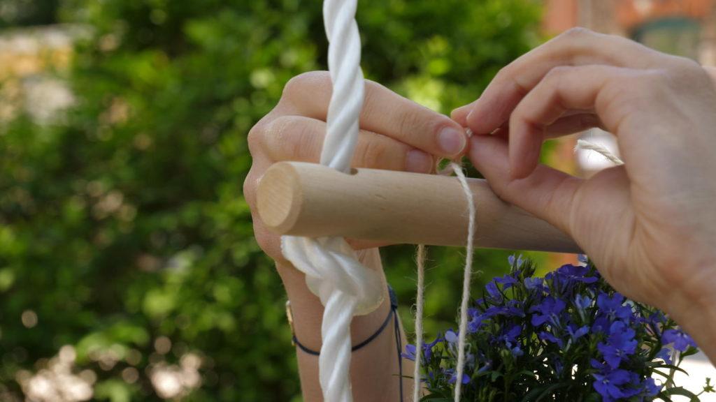 Blumentopf wird an einer Sprosse einer Strickleiter angebunden