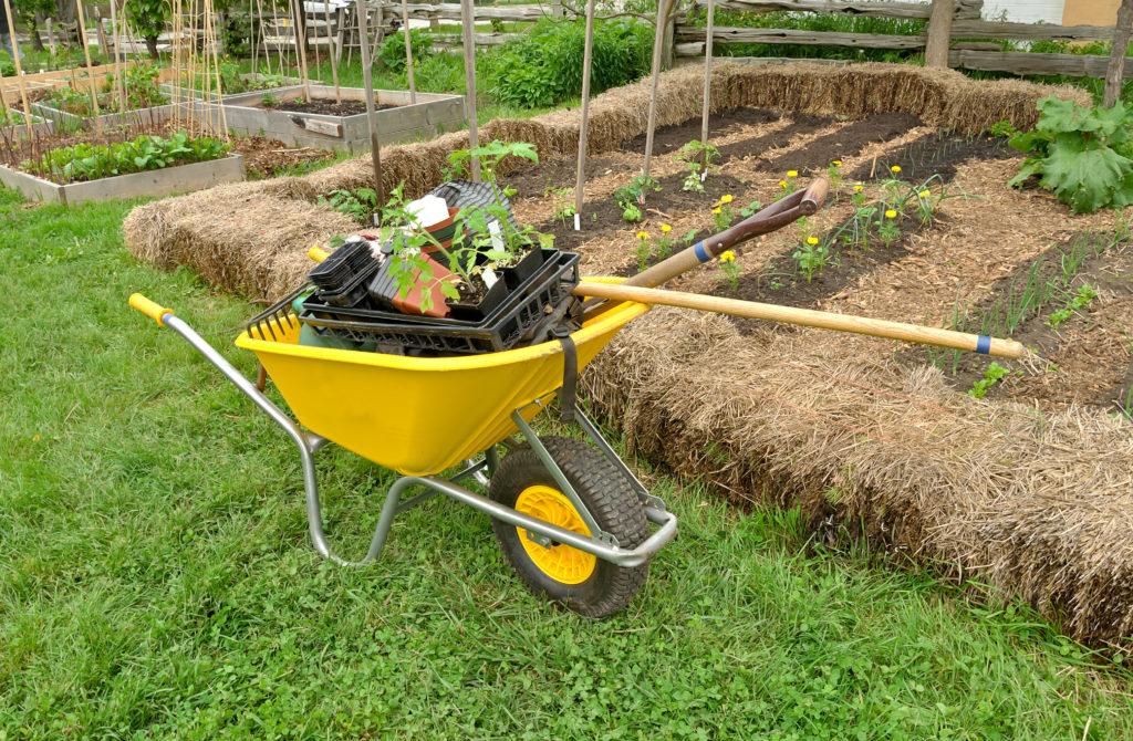 Gartenwerkzeuge neben Strohgarten