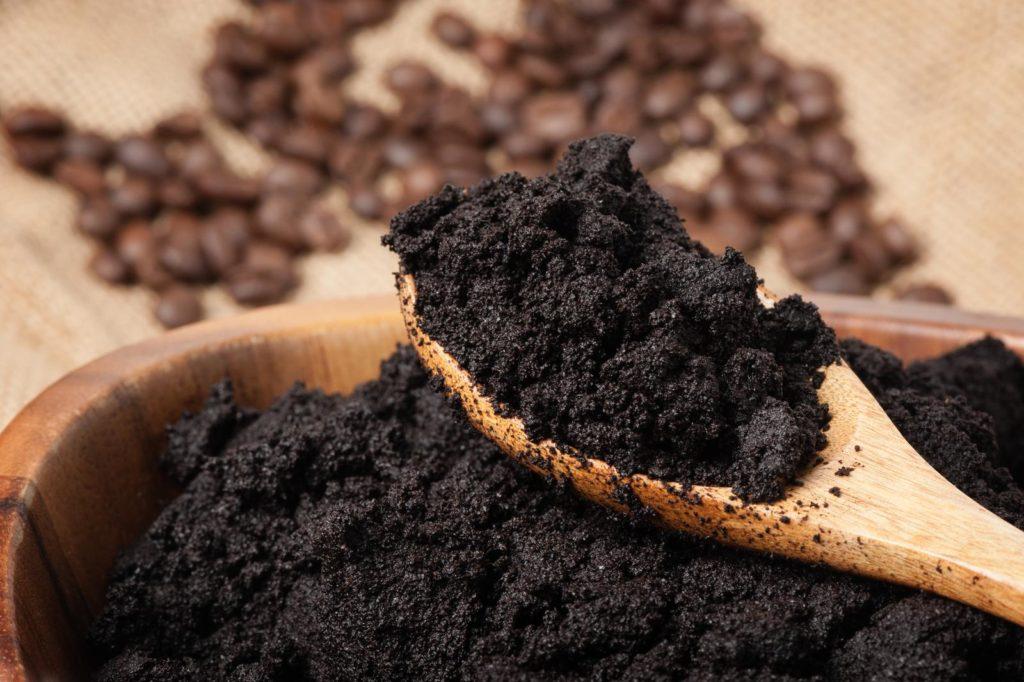 Kaffeesatz in einer Holzschüssel mit Löffel
