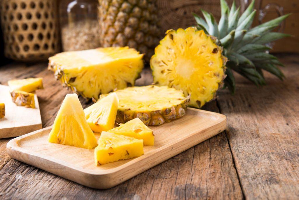 Aufgeschnittene Ananas auf Holzbrett
