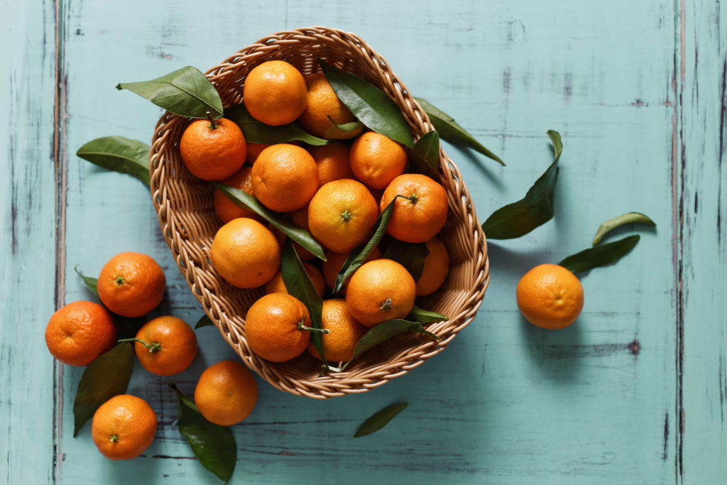 Mandarinen mit Blättern in Korb