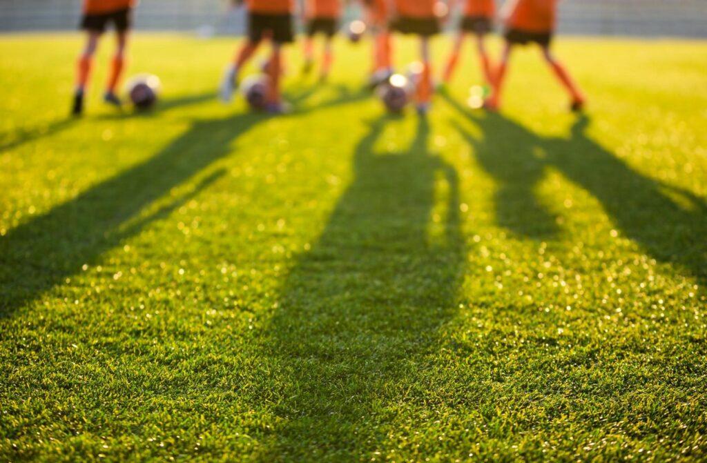 Rasen mit Fußballer im Hintergrund