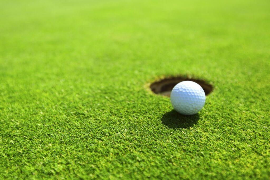 Golfrasen mit Loch und Golfball