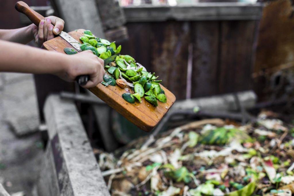 Bio-Abfall in Kompost werfen