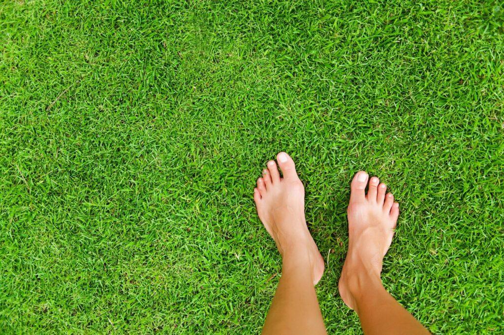 Nackte Füße auf Rasen