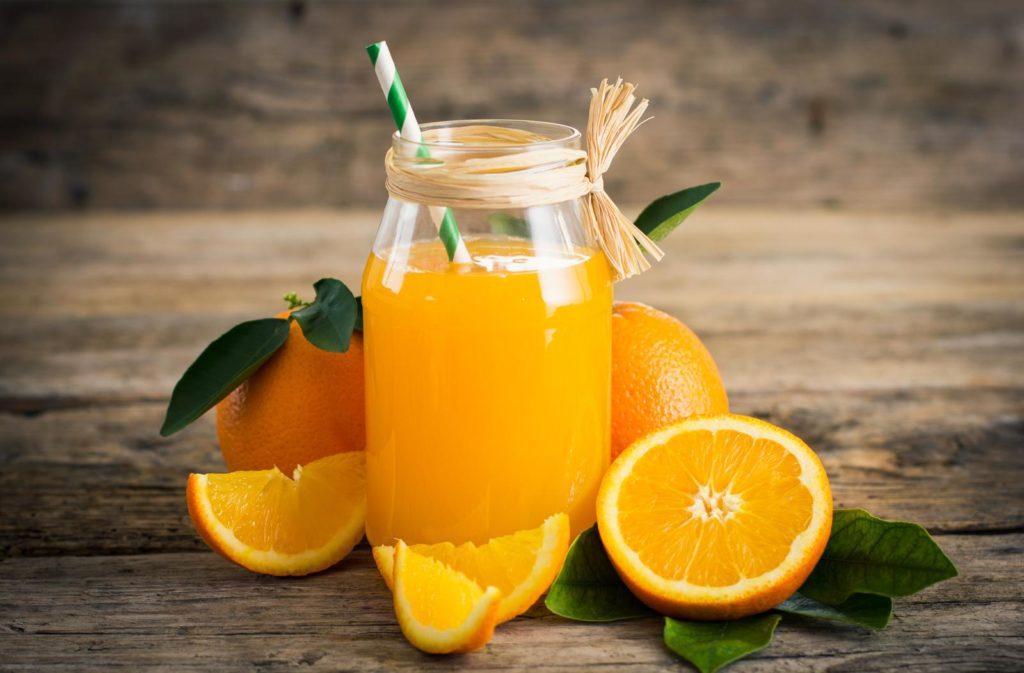 Orangen aufgeschnitten und Saft auf Tisch