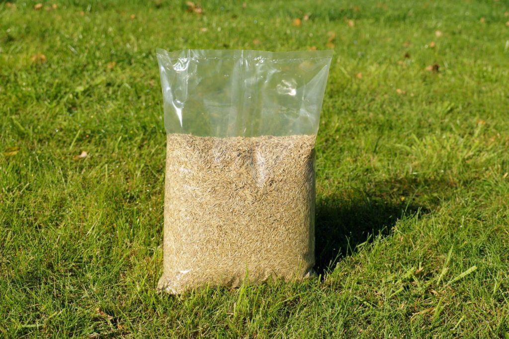 Sack mit Rasensamen auf Rasen stehend