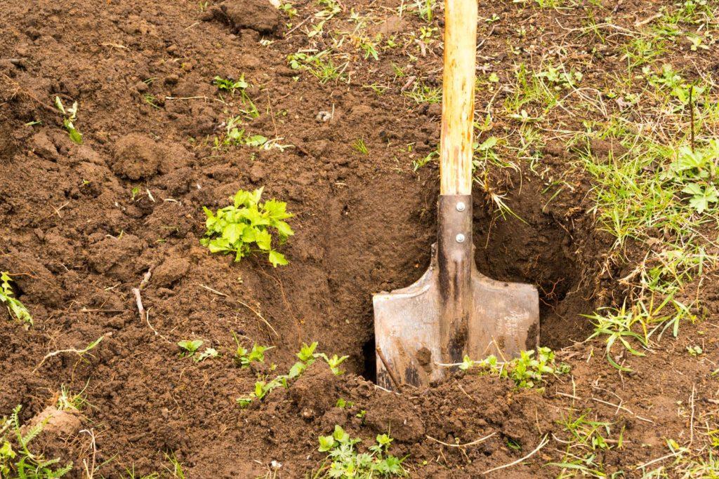 Loch mit Schaufel graben