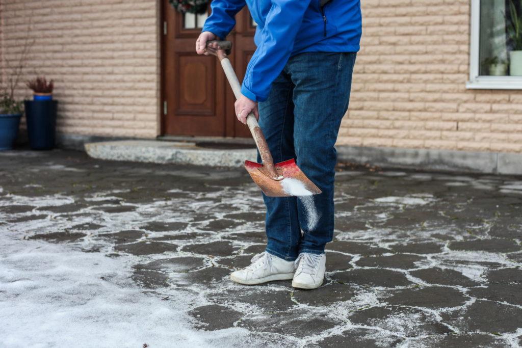 Streusalz von Mann in Einfahrt verteilt