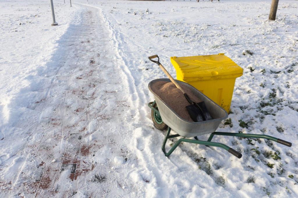 Verschneiter Weg mit Sand in Schubkarre