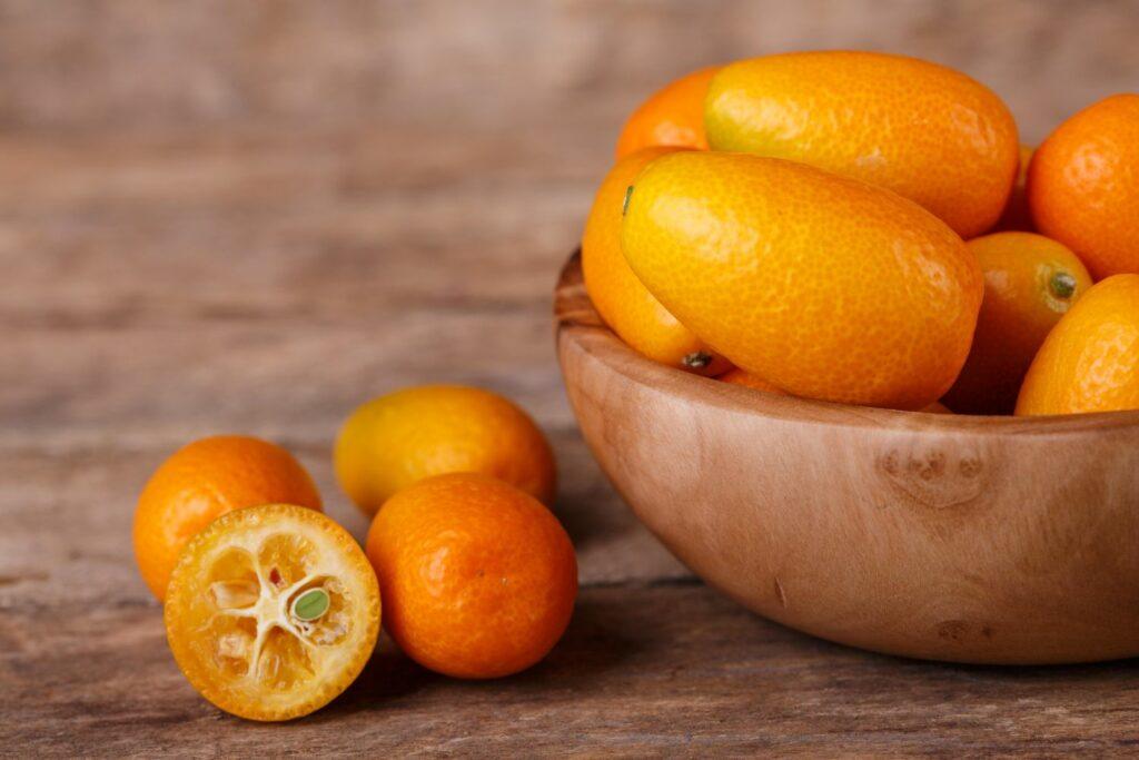 Aufgeschnittene Kumquat neben einer Schale Kumquats