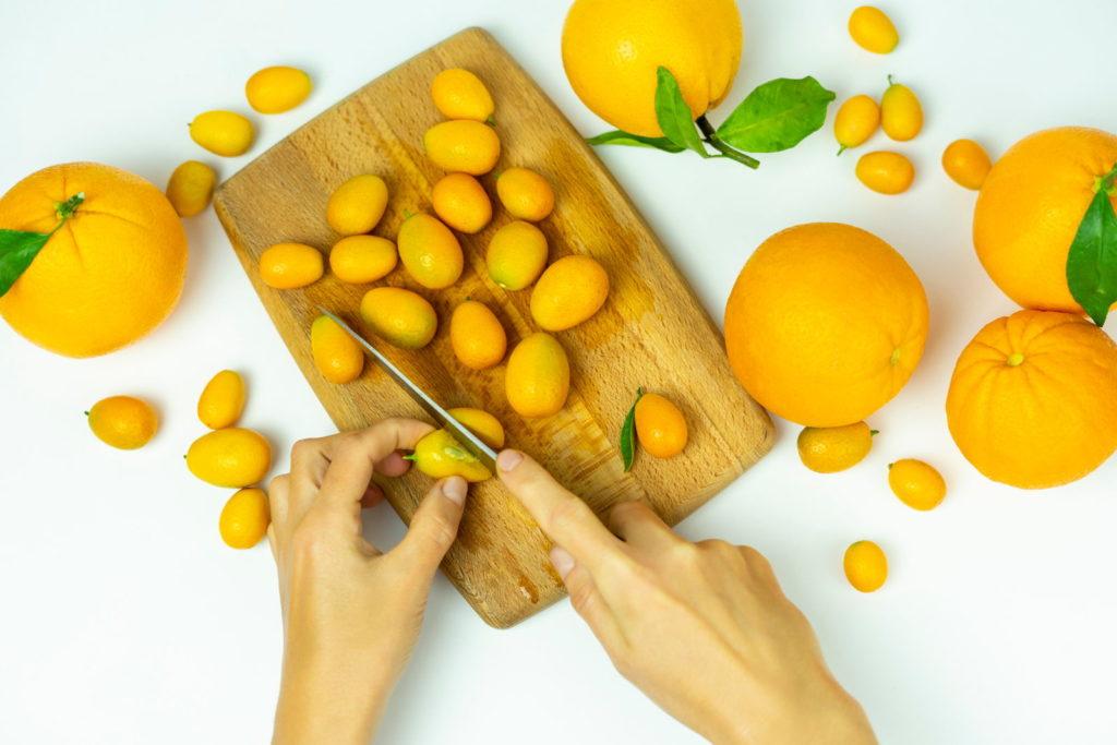 Kumquats werden mit einem Messer geschnitten