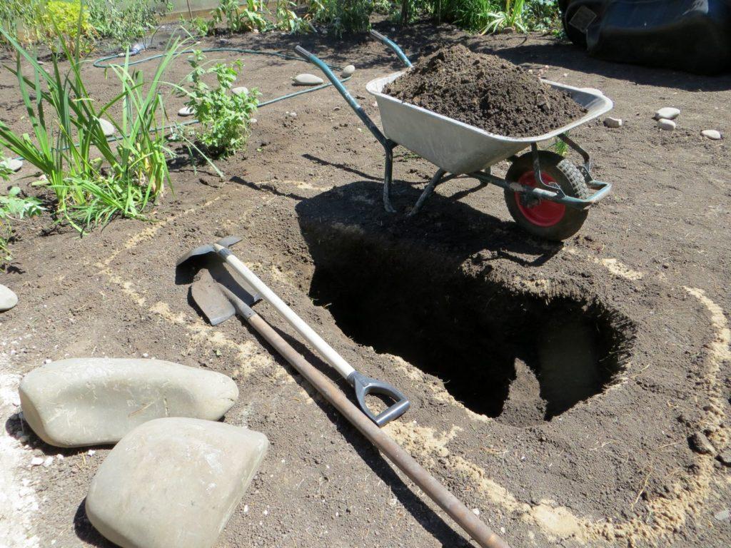 Loch in der Erde mit einem Schubkarren im Garten